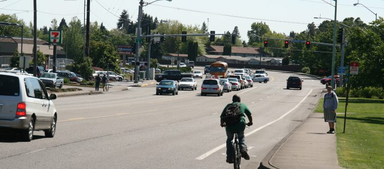 Photo of the streetscape looking toward the River Rd N at Lockhaven intersection showing vehicles, a bicyclist and person waiting for transit.